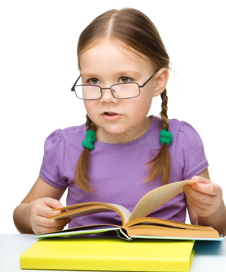 Vidros desgastando bonitos do livro de leitura da menina fotos de stock