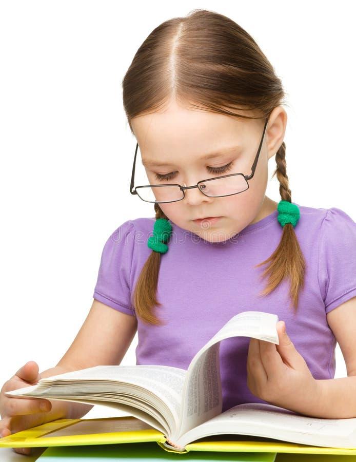 Vidros desgastando bonitos do livro de leitura da menina imagens de stock royalty free