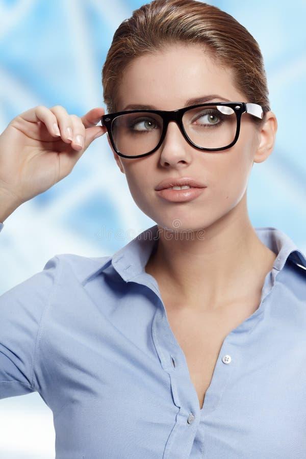 Vidros desgastando da mulher no escritório imagem de stock