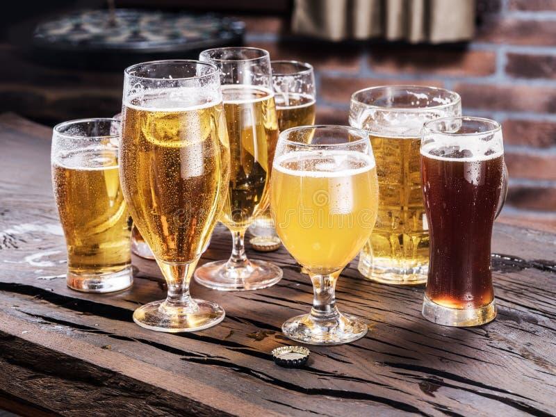 Vidros diferentes da cerveja na tabela de madeira imagens de stock royalty free