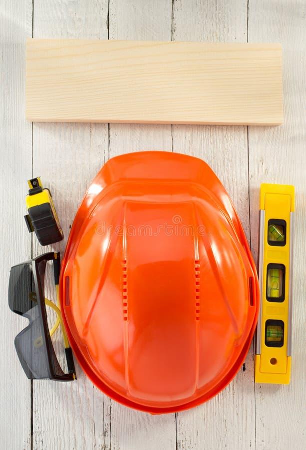 Vidros do capacete e de segurança da construção na madeira imagem de stock