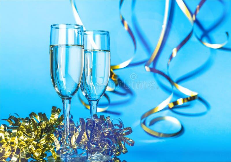 Vidros do champanhe com as fitas encaracolado na obscuridade imagens de stock