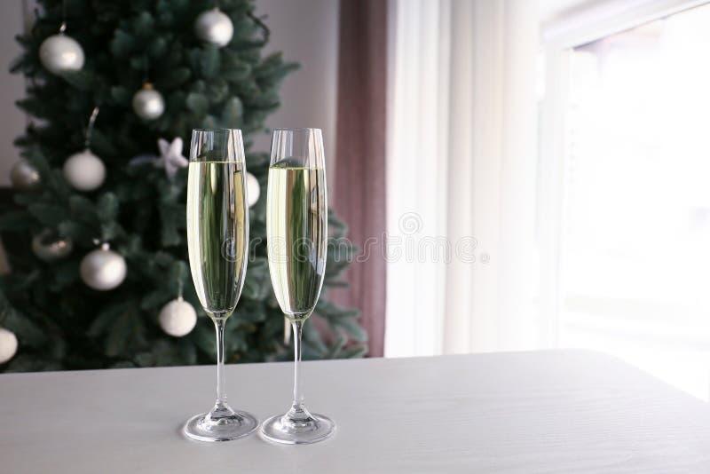 Vidros do champanhe na tabela na sala decorada para o Natal fotos de stock
