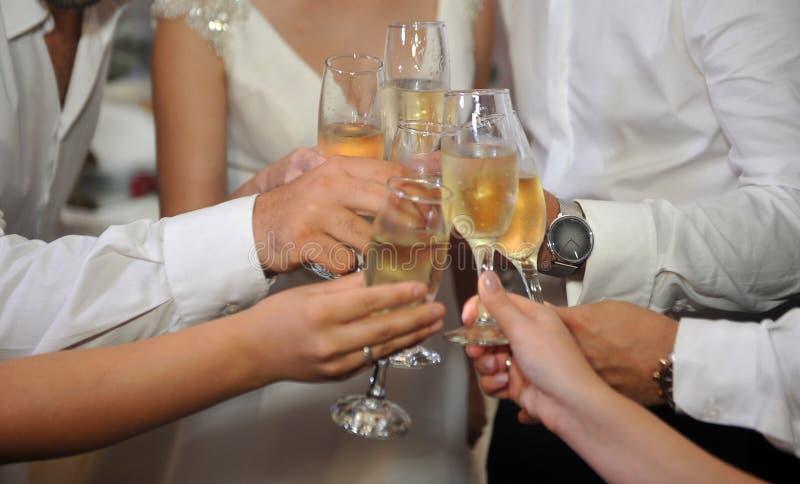 Vidros do champanhe nas mãos dos convidados em um casamento fotografia de stock royalty free
