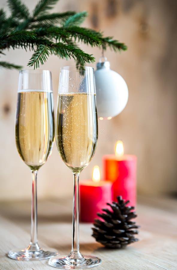 Vidros do champanhe sob o ramo de árvore decorado do Natal imagem de stock