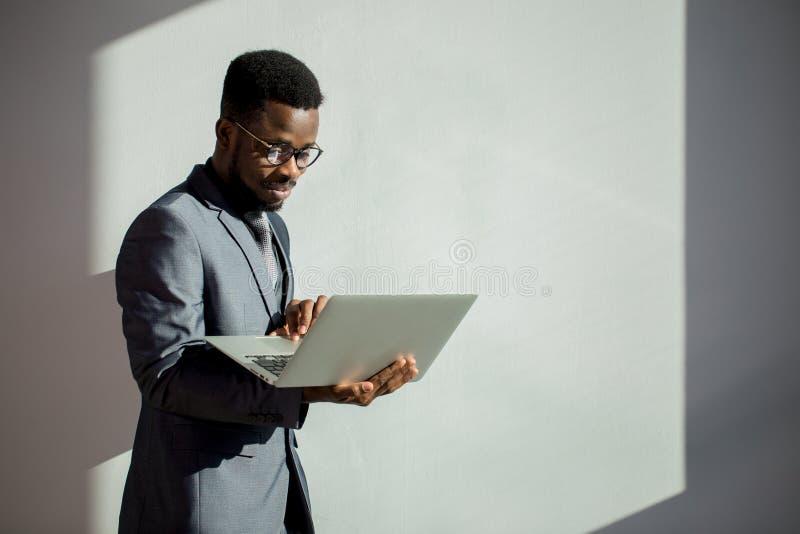 Vidros do colega de trabalho africano e portátil vestindo da utilização no escritório fotos de stock