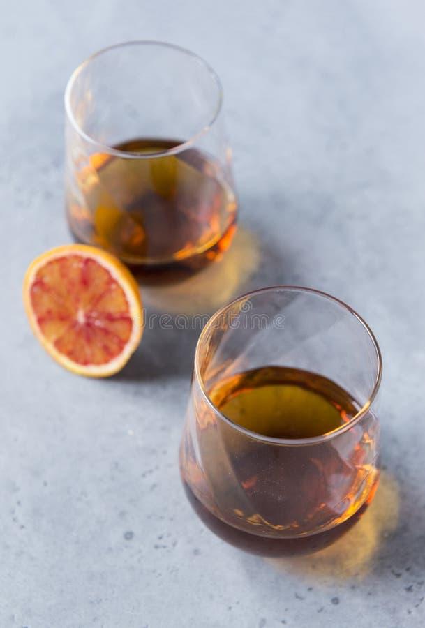 2 vidros do conhaque em um fundo cinzento, uma parte de laranja fotografia de stock