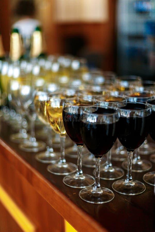Vidros do fundo do vinho branco e da garrafa de vinho tinto na tabela imagem de stock