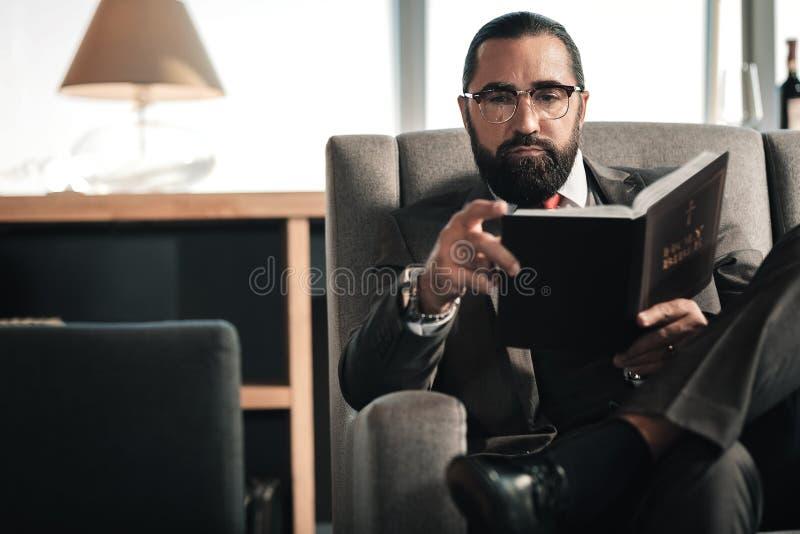 Vidros do homem farpado e relógio vestindo da mão que guarda a Bíblia fotos de stock royalty free