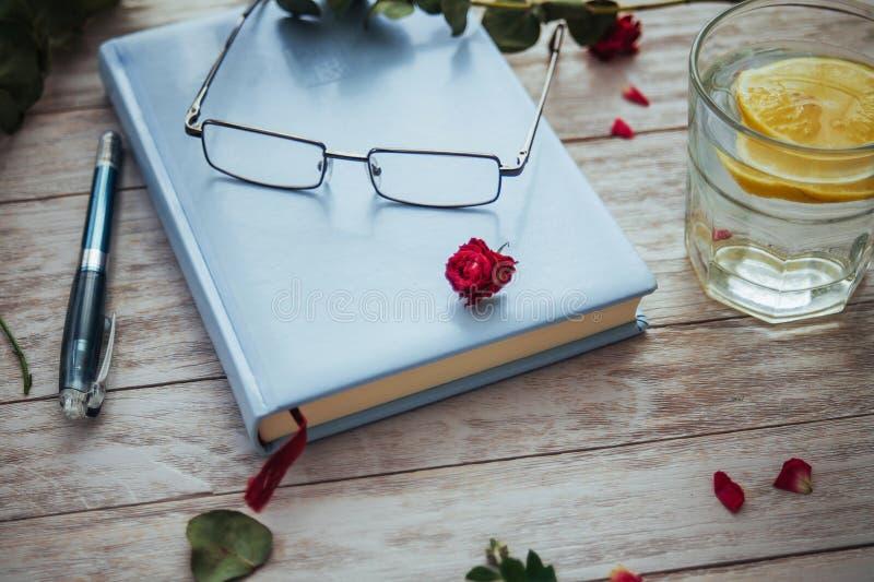 vidros do livro e pétalas da flor imagem de stock royalty free