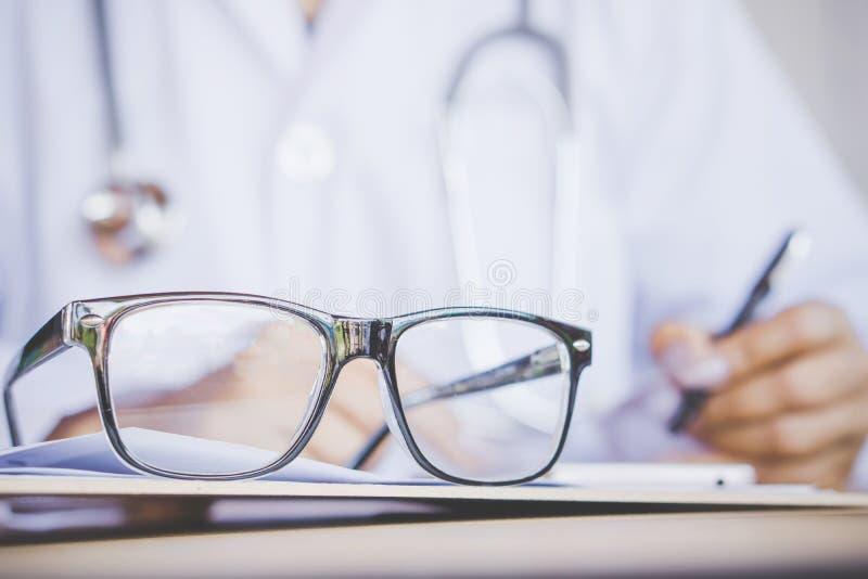 Vidros do olho na mesa com o fundo do borrão do doutor que escreve a prescrição fotos de stock