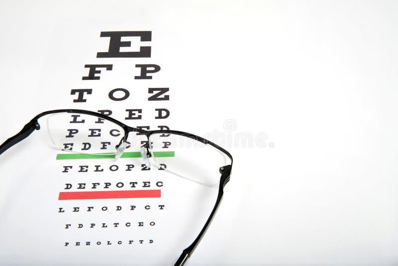 Vidros do olho no fim do fundo da carta de teste da visão acima fotografia de stock