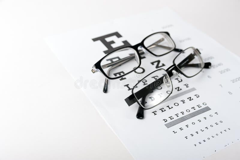 Vidros do olho no fundo da carta de teste da visão fotografia de stock royalty free
