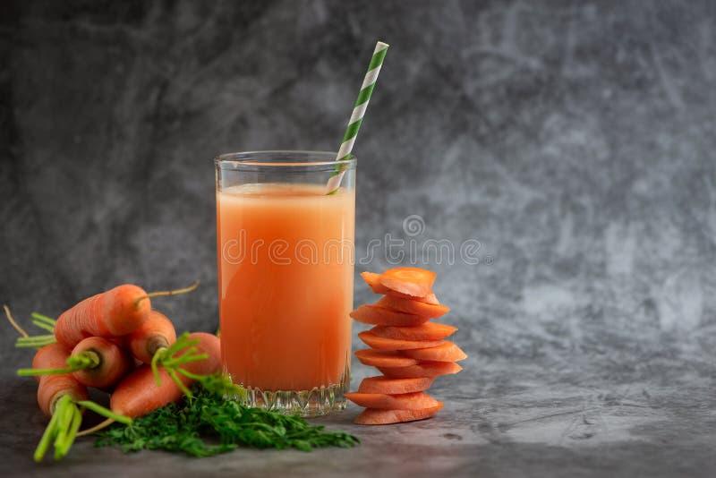 Vidros do suco de cenoura com os vegetais na tabela cinzenta Vista lateral imagem de stock royalty free