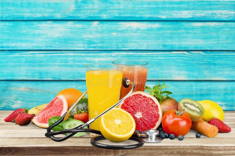 Vidros do suco e de frutos frescos com estetoscópio fotos de stock royalty free