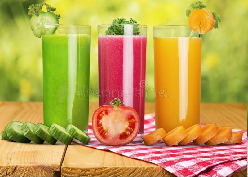 Vidros do suco e de vegetais frescos na tabela foto de stock royalty free