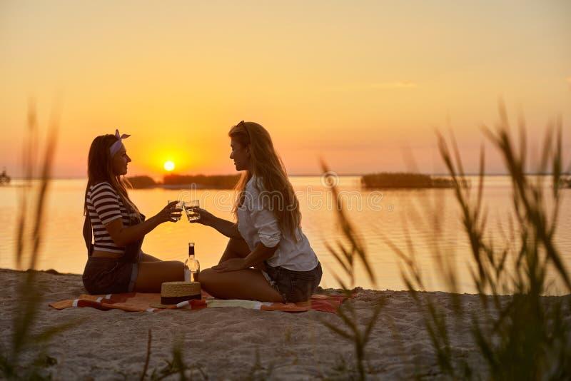 Vidros do tim-tim das mulheres com vinho branco na praia As amigas alegremente comemoram férias e proclamam o brinde sobre imagens de stock