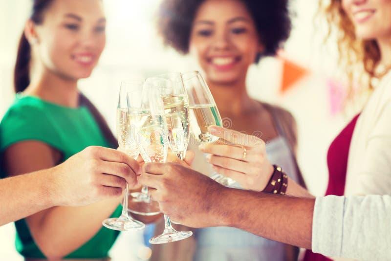Vidros do tinido dos amigos do champanhe no partido foto de stock
