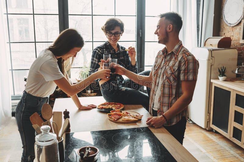 Vidros do tinido dos amigos com vinho e comer a peça da pizza em casa foto de stock