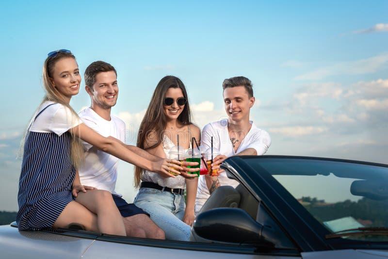 Vidros do tinido dos amigos da limonada ao sentar-se no cabriolet foto de stock royalty free