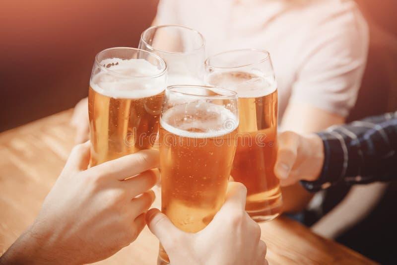 Vidros do tinido dos amigos em restaurantes da cerveja imagem de stock