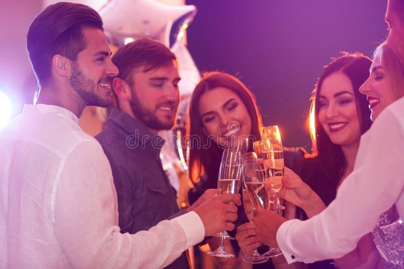 Vidros do tinido dos jovens com champanhe na festa de anos no clube fotos de stock royalty free