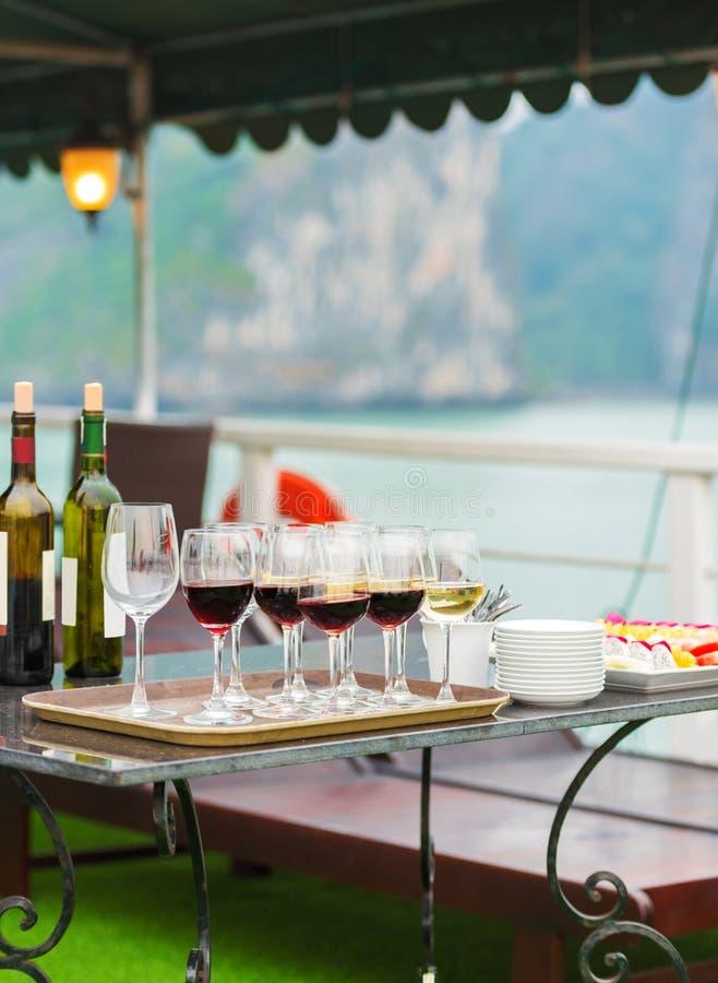 Vidros do vinho na plataforma do navio, Halong, Vietname vertical foto de stock royalty free