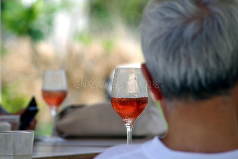 Vidros do vinho do rosé em uma tabela com uma parte traseira de um homem no primeiro plano fotografia de stock royalty free