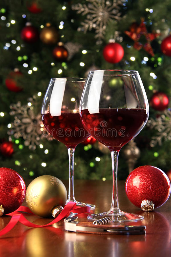 Vidros do vinho vermelho na frente da árvore de Natal fotografia de stock royalty free