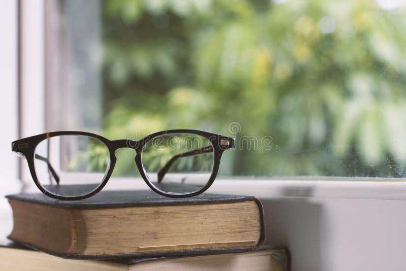 Vidros do vintage em livros ao lado de uma janela foto de stock royalty free
