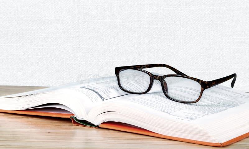 Vidros e livro pretos de leitura do close-up no borrado imagens de stock royalty free