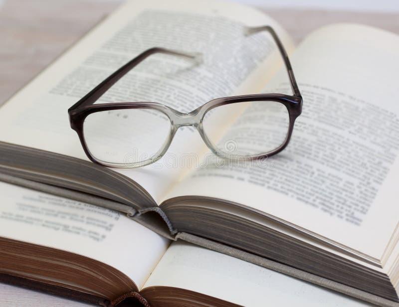 Vidros e livros abertos na tabela imagem de stock
