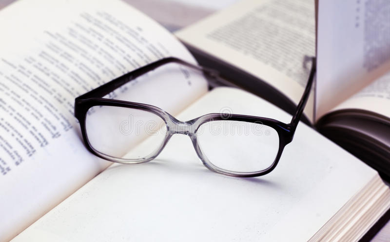 Vidros e livros abertos na tabela foto de stock royalty free