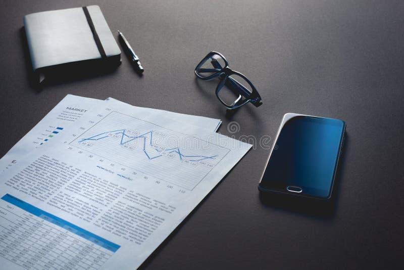 Vidros e mentira do telefone em um fundo preto ao lado de um bloco de notas cinzento fotografia de stock