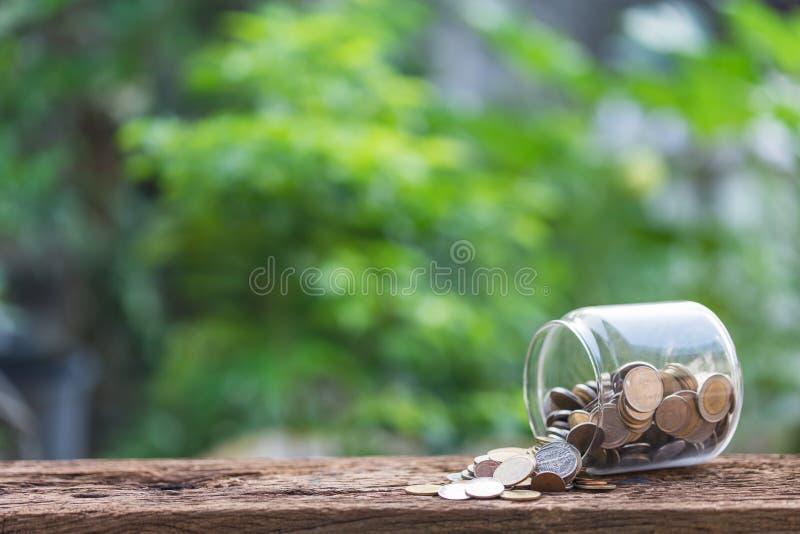 Vidros e moedas na queda na tabela com fundo verde foto de stock royalty free