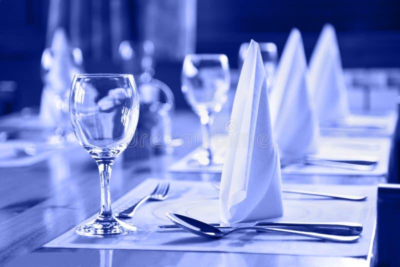 Vidros e placas na tabela no restaurante imagem de stock