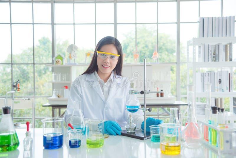 Vidros e revestimento vestindo de segurança do químico que sentam-se no laboratório imagens de stock royalty free