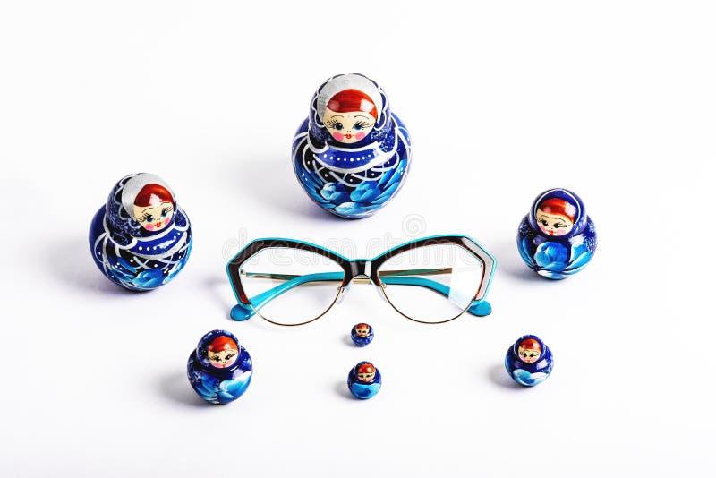 Vidros em um quadro azul e bonecas azuis do aninhamento em um fundo branco foto de stock royalty free