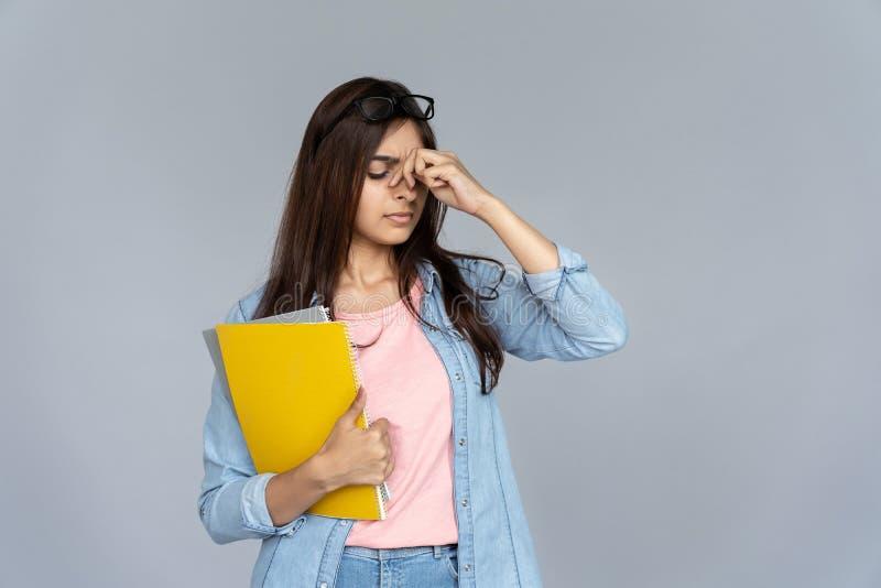 Vidros indianos cansados da tensão de olho da sensação do estudante de mulher isolados no fundo cinzento imagens de stock royalty free