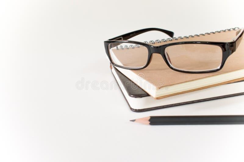Vidros, livro e lápis no fundo branco fotos de stock