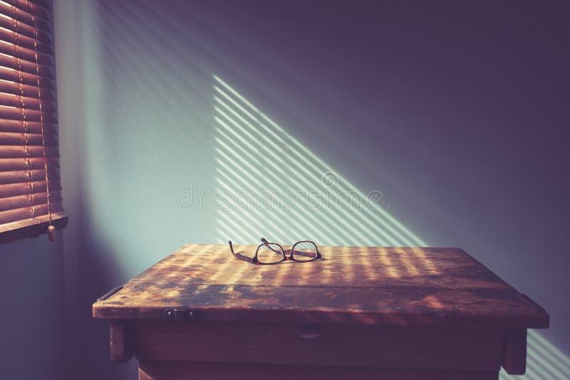 Vidros na mesa pela janela imagens de stock