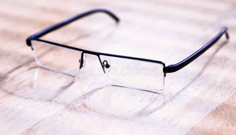 Vidros no quadro preto no fundo de madeira, tabela A vista da parte superior imagem de stock
