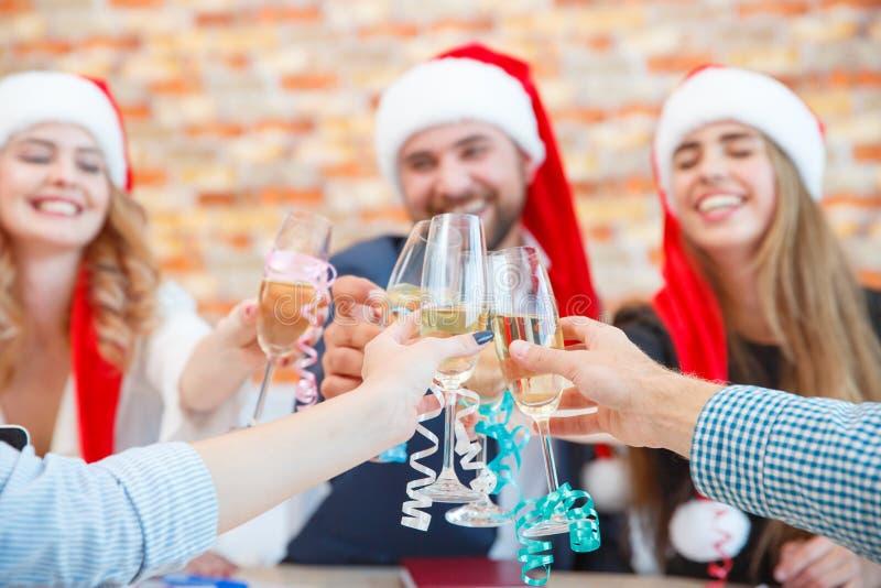 Vidros novos bonitos do tinido dos amigos do close-up no Natal em um fundo borrado Conceito dos feriados de inverno fotografia de stock royalty free