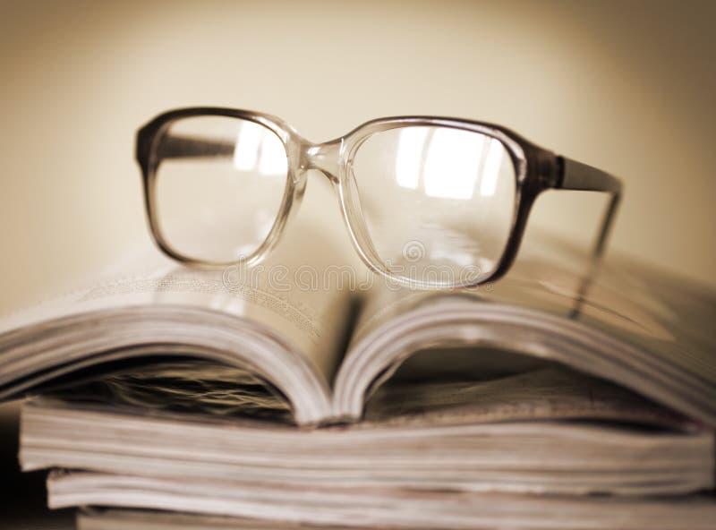 Vidros para ler em uma pilha de compartimentos, no foco macio imagem de stock