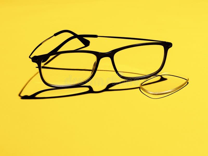 Vidros quebrados, monóculos, lente caída para fora no fundo amarelo para o copyspace Saúde ótica ou eyewear imagens de stock