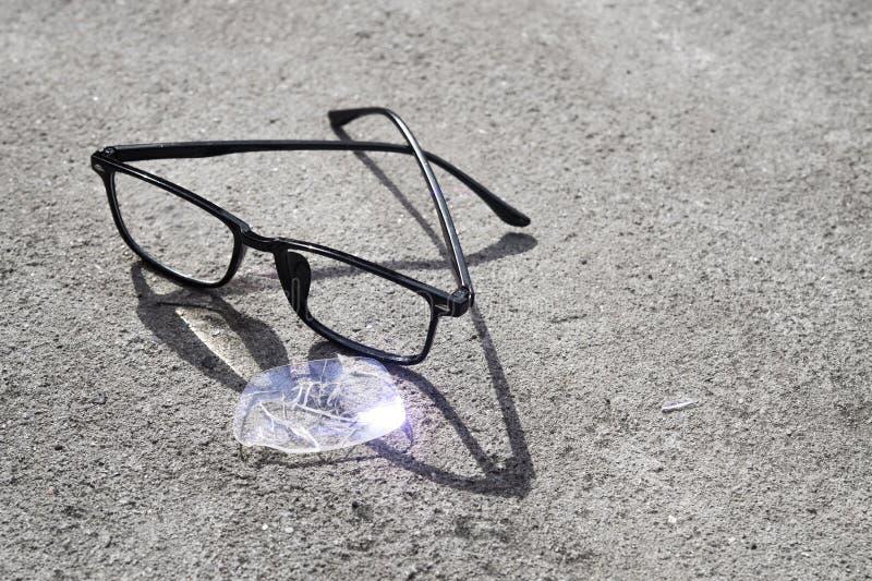 vidros quebrados que encontram-se no asfalto da rua imagens de stock