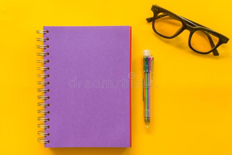 Vidros roxos do caderno da pena roxa no fundo amarelo imagem de stock