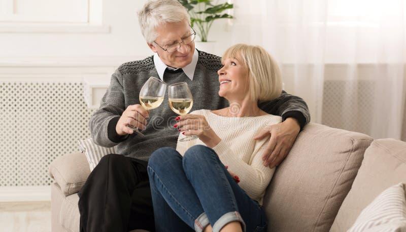 Vidros superiores felizes do tinido dos pares do vinho branco foto de stock