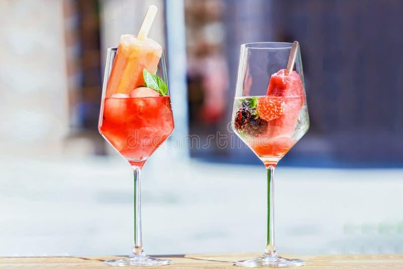 Vidros transparentes do vinho, dos picolés, da melancia, da morango, da amora-preta e da hortelã fotos de stock royalty free