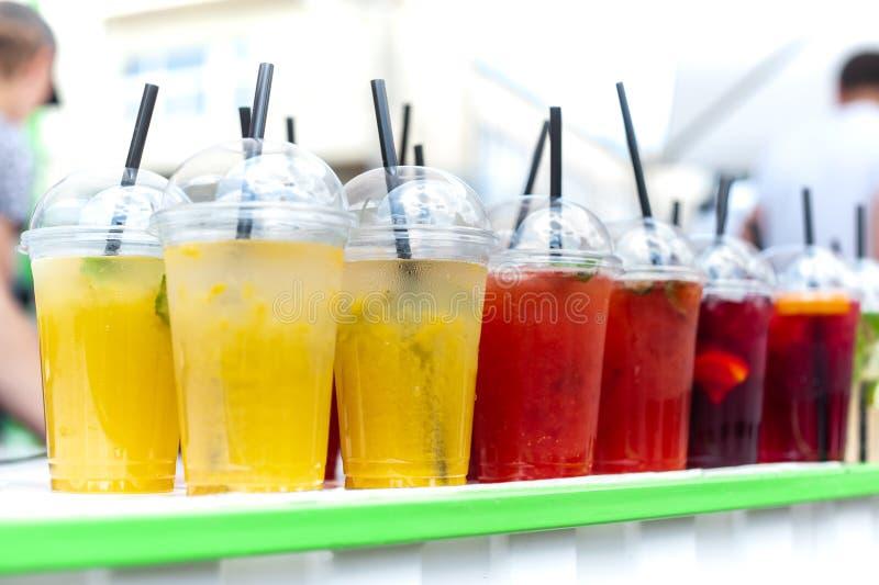 Vidros transparentes plásticos com tipos diferentes de estadas frias da limonada (amarelo, vermelho, verde) na tabela branca com  imagem de stock